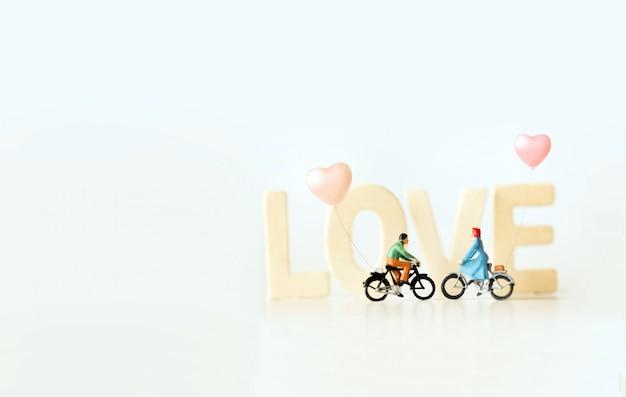 「love」テキストで自転車に乗って幸せな若いカップルのミニチュア。ヴィンテージの色をテーマにしたバレンタインの日。 Premium写真