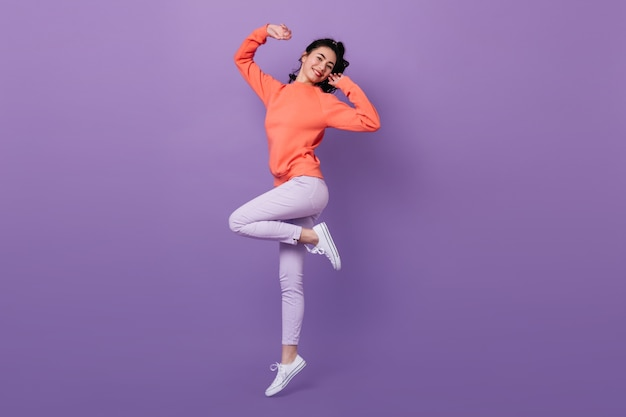 Lovely asian woman standing on one leg. full length view of attractive stylish japanese woman jumping on purple background. Free Photo