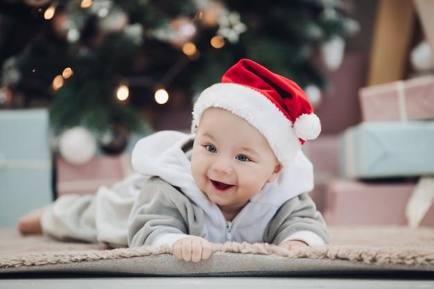 Прекрасный мальчик в сером костюме и красной шляпе санты, лежащей на ковре против размытого рождественского дерева. Premium Фотографии