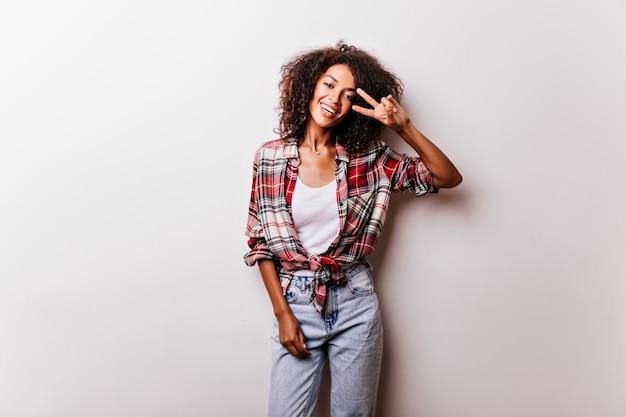 ピースサインでポーズをとるヴィンテージデニムパンツの素敵な黒人の女の子。白で隔離の市松模様のシャツの熱狂的な女性モデル。 無料写真