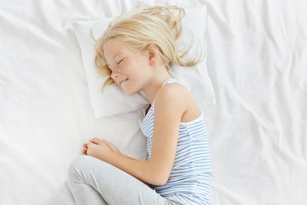 ボールにロールアップする白い枕に甘い夢を持っている素敵なブロンドの女の子。彼女の快適なベッドルームで穏やかな雰囲気を楽しんで、光のストレートの髪が眠りに笑みを浮かべてかなりそばかすのある女の子 無料写真