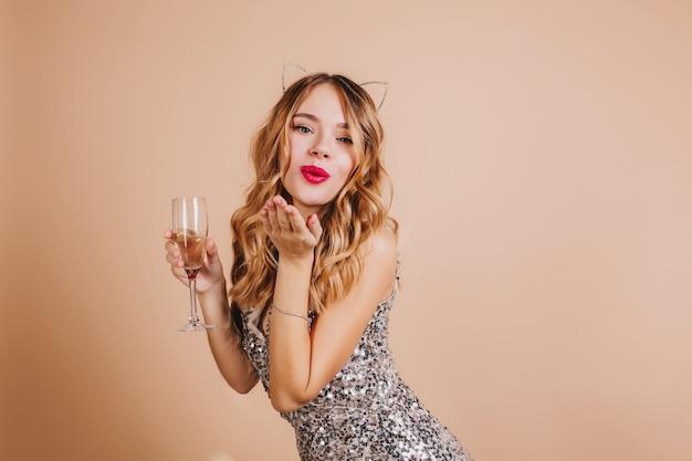 와인 글라스와 빛 벽에 서 공기 키스를 보내는 스파클 복장에 사랑스러운 금발의 여자 무료 사진