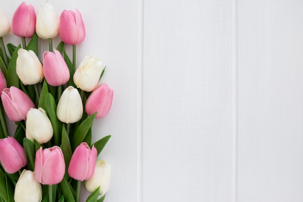 Lovely bouquet of tulips on white wooden background with copyspace to the right Free Photo