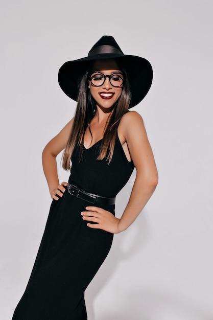 Прекрасная яркая женщина в костюме ведьмы позирует над изолированной стеной с прекрасной улыбкой. привлекательная стильная модель готовится к хэллоуину Бесплатные Фотографии
