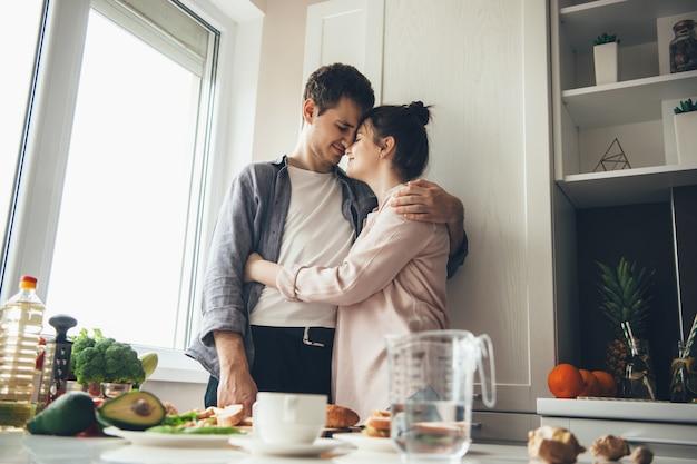Прекрасная кавказская пара на кухне, обнимая, вместе готовя еду Premium Фотографии