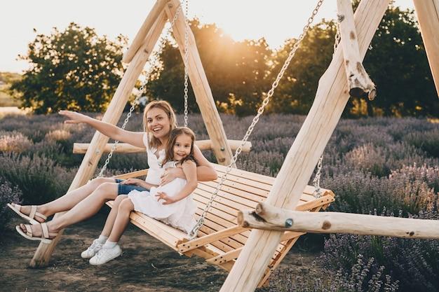 사랑스러운 백인 어머니와 배경에 라벤더 밭과 그네에 앉아 그녀의 작은 딸 프리미엄 사진