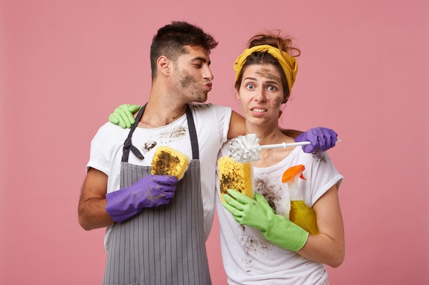 Прекрасное купе: красивый мужчина обнимает ее жену и хочет поцеловать ее, помогая ей убирать в доме Бесплатные Фотографии