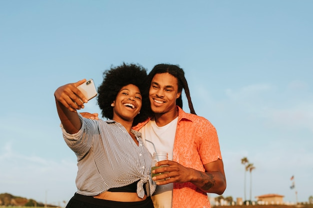 Lovely couple taking a selfie at the beach Premium Photo