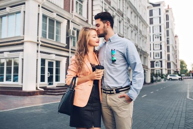 ブリティッシュクォーターを歩く素敵なカップル。コーラルジャケットと黒のドレスで頭のブロンドの女の子にキス青いシャツを着て黒髪の男。 無料写真
