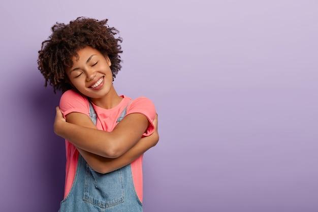 Милая кудрявая женщина с удовольствием обнимает себя, ощущает комфорт, спокойствие и любовь, наклоняет голову и положительно улыбается, с закрытыми глазами, позирует над фиолетовой стеной, пустое пространство Бесплатные Фотографии