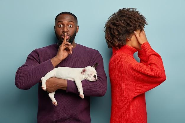 素敵な巻き毛の女性が立ち上がって目を覆い、夫からの驚きを待ちます。浅黒い肌の男は沈黙のジェスチャーをし、彼が何を提示しようとしているのかわからないように頼み、小さな眠っている犬を抱き、贈り物をします 無料写真