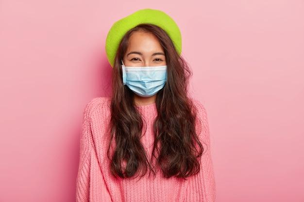 Bella signora asiatica dai capelli scuri ha una malattia epidemica, indossa una maschera medica protettiva, un berretto verde e un maglione Foto Gratuite