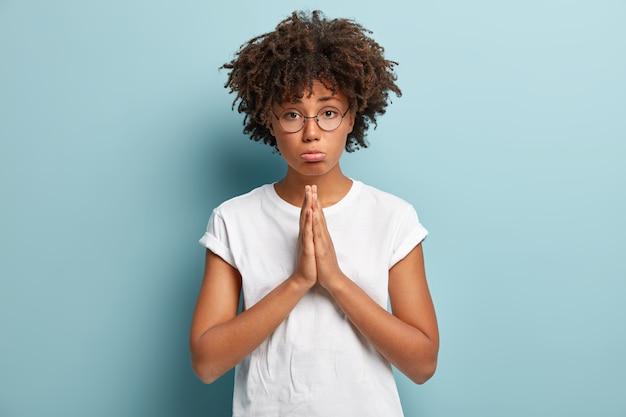 哀れな表情の素敵な黒い肌の女の子、手のひらを押し付け続け、何かを求め、希望に満ちた視線を持ち、謝罪を求め、お金を貸してくれと頼み、光学眼鏡と白いtシャツを着ています 無料写真