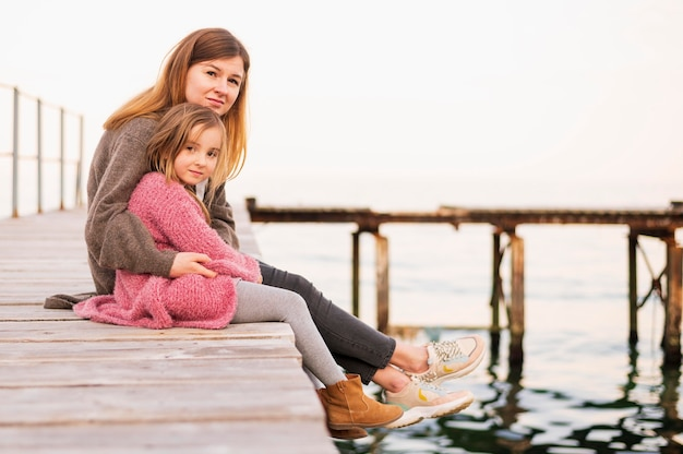 Lovely daughter and mother sitting Free Photo