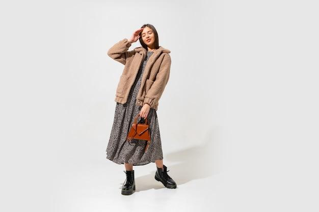 세련된 모피 코트와 드레스에 사랑스러운 유럽 모델. 블랙 가죽 소재의 앵클 부츠를 신고 있습니다. 갈색 핸드백을 들고. 무료 사진