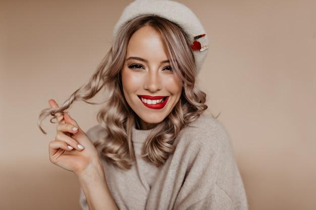 갈색 벽에 그녀의 곱슬 머리를 가지고 노는 사랑스러운 프랑스 여자 무료 사진