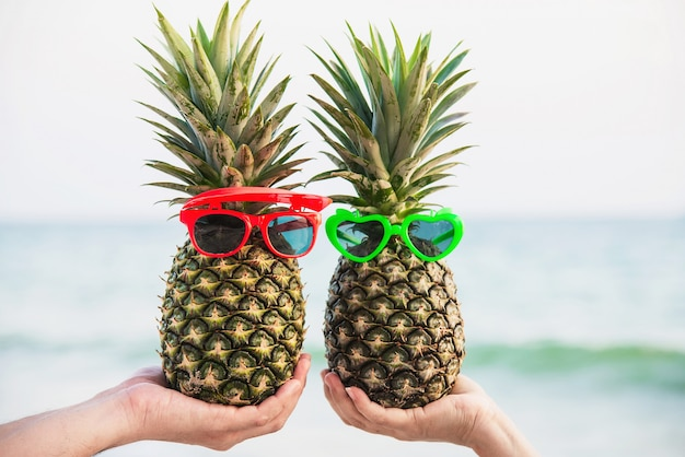 Lovely fresh couple pineapples putting glasses in tourist hands with sea wave - happy love and fun with healthy vacation concept Free Photo
