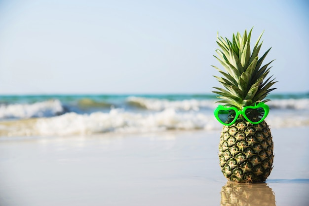 Lovely fresh pineapple put heart shape sun glasses on clean sand beach with sea wave - fresh fruit with sea sand sun vacation concept Free Photo
