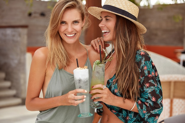 Lovely gay female couple enjoy good recreateion in exotic country, embrace and have good mood, enjoy cold fresh cocktails, wear summer clothing. cheerful woman in straw hat stands near friend Free Photo
