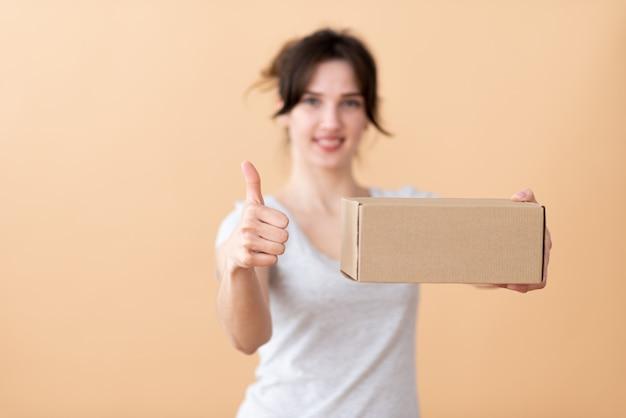 素敵な女の子は手でクラフトボックスを保持し、ベージュの空間に親指でクラスを示しています。 Premium写真