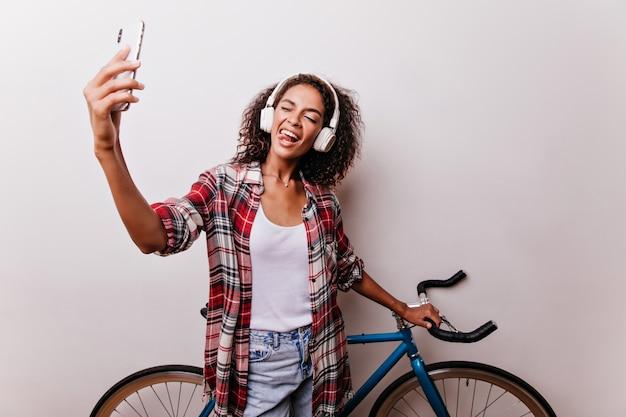 Bella ragazza che fa selfie accanto alla bicicletta blu. studio shot di bella donna africana scherzare mentre si scatta una foto di se stessa. Foto Gratuite