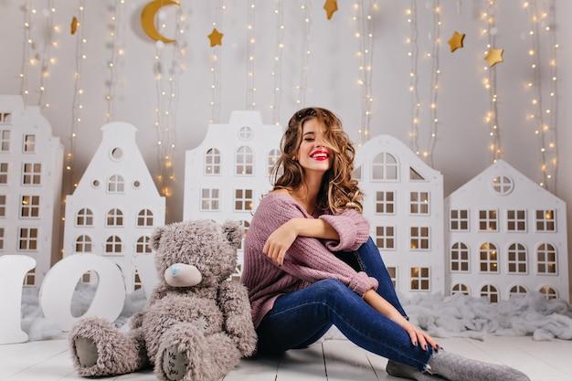 25歳の素敵な女の子は、明るい金色の星のような暖かい装飾が施された白い壁にテディのおもちゃを持って床に座っています 無料写真