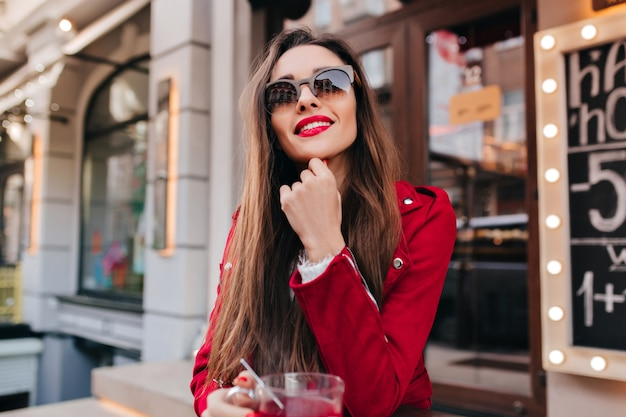 Bella ragazza in occhiali da sole e giacca rossa in posa con un sorriso interessato Foto Gratuite