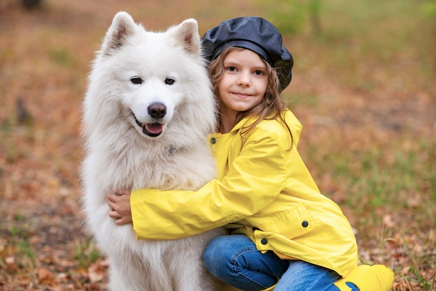 Lovely girl on a walk with a beautiful dog in a park outdoor Premium Photo