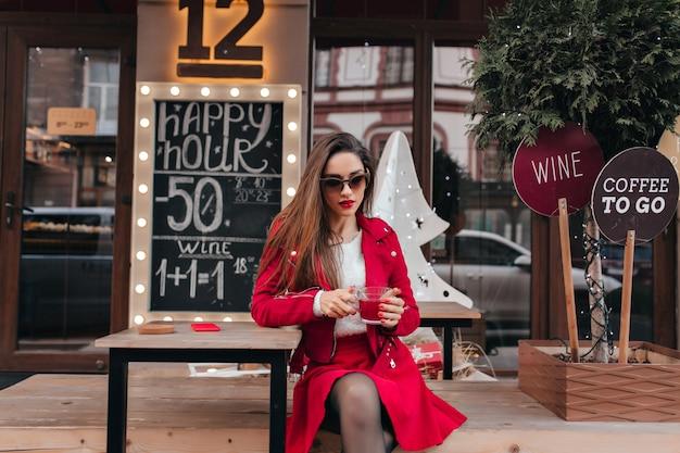 Bella ragazza indossa occhiali da sole e gonna rossa seduti in un caffè all'aperto Foto Gratuite