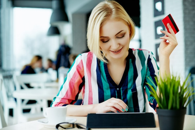 Lovely girl with light hair wearing colorful shirt sitting in cafe with tablet, credit card and cup of coffee, freelance concept, online shopping. Premium Photo