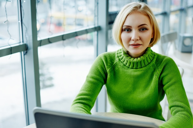 Lovely girl with light hair wearing green sweater sitting in cafe with laptop, portrait, freelance concept, online shopping. Premium Photo