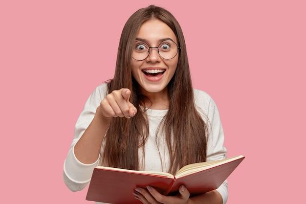 Милая радостно удивленная девушка широко улыбается и указывает прямо в камеру Бесплатные Фотографии