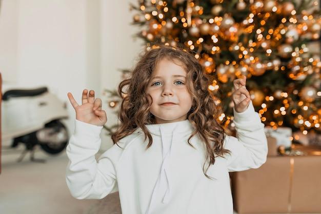 곱슬 머리와 사랑스러운 행복 한 어린 소녀 흰색 니트 옷을 입고 손을 위로 크리스마스 트리 앞에서 웃 고 무료 사진