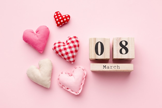 Lovely hearts on pink background with 8 march lettering Free Photo