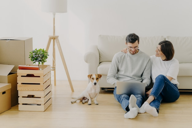 Lovely husband and wife sit in new apartment with laptop computer Premium Photo
