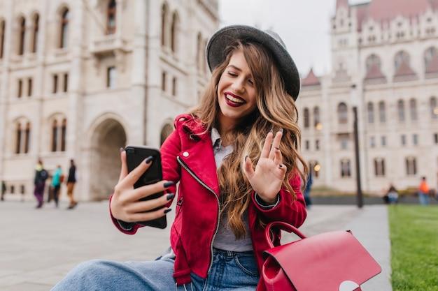 Bella studentessa internazionale che fa selfie davanti al vecchio bellissimo edificio Foto Gratuite