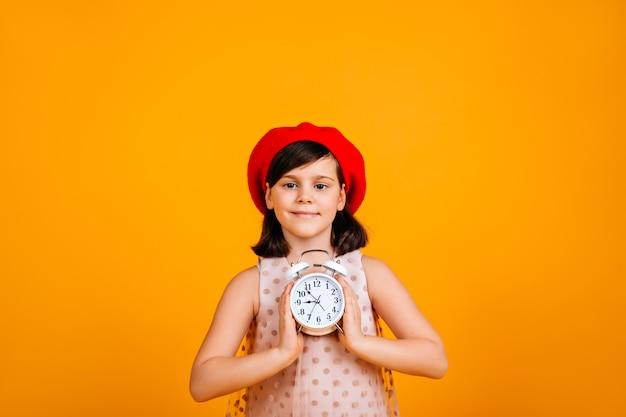 Ragazzo adorabile che tiene grande orologio. bambino caucasico entusiasta isolato sulla parete gialla. Foto Gratuite
