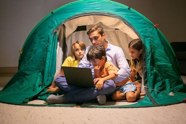Прекрасные дети отдыхают с отцом в палатке дома и смотрят фильм на портативном компьютере. симпатичные дети и папа средних лет сидят и веселятся вместе. детство, семейное время и концепция выходных Бесплатные Фотографии