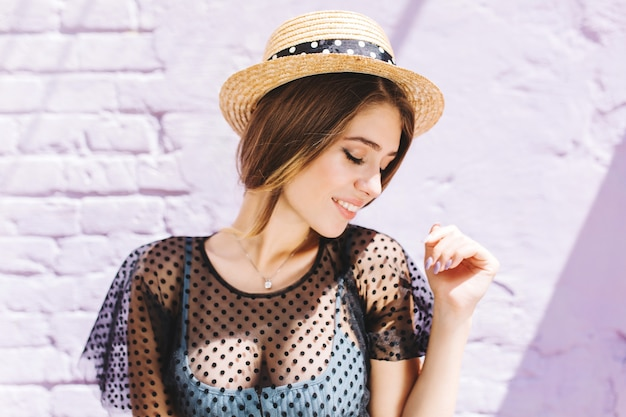 Lovely lady wears vintage hat and silver necklace looking away while posing near old white wall Free Photo