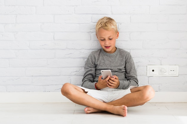 Lovely little boy using his smartphone Free Photo