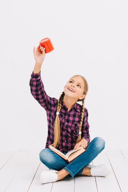 Lovely little girl reading a book and holding a mug Free Photo