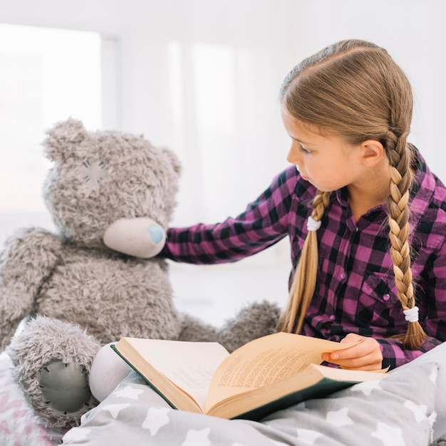 Lovely little girl reading a book with her teddy bear Free Photo