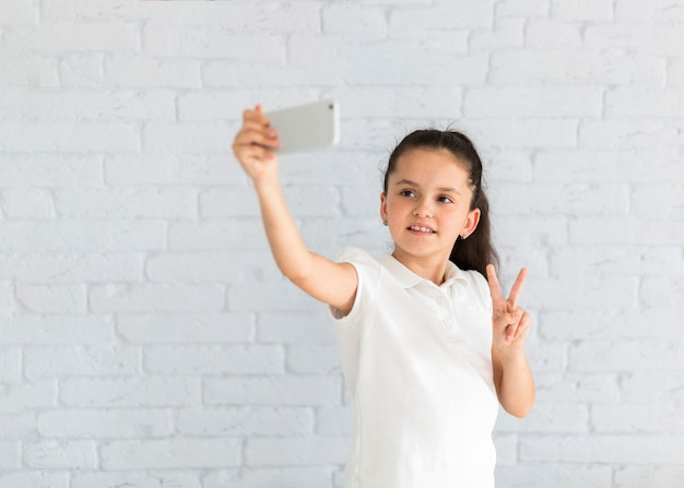 Lovely little girl taking a selfie Free Photo