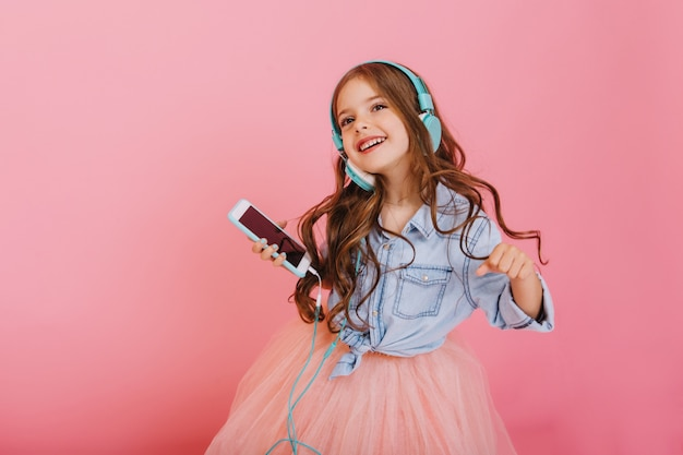 Lovely moments of little child enjoying music through headphones, dancing with phone isolated on pink background. expressing true positive emotions of fashionable happy child at entertainment Free Photo