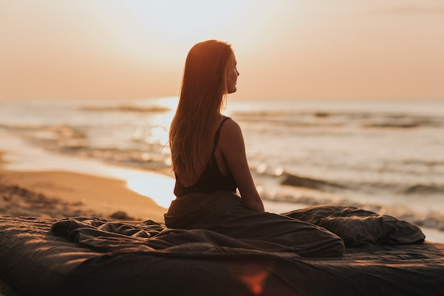 Lovely morning sunrise at sea, silhouette of the girl at sunset. woman relaxes by the sea. meditation concept Premium Photo