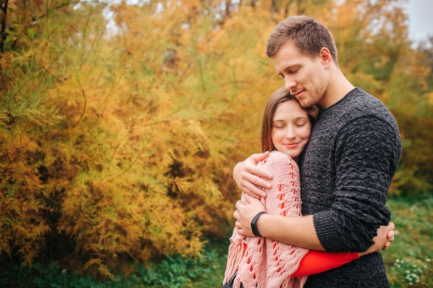 Lovely picture of couple embracing. they keep eyes closed and enjoying the moment. people stand in autumn park. Premium Photo