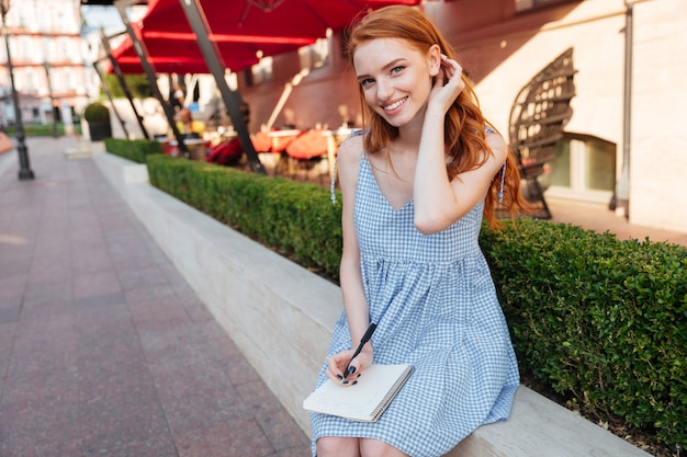 Lovely redhead girl holding notepad and a pen Free Photo