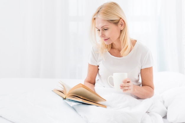 Lovely senior woman reading a book while having coffee Free Photo