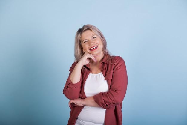 Прекрасная старшая женщина трогает ее подбородок и улыбается на синей стене студии Premium Фотографии