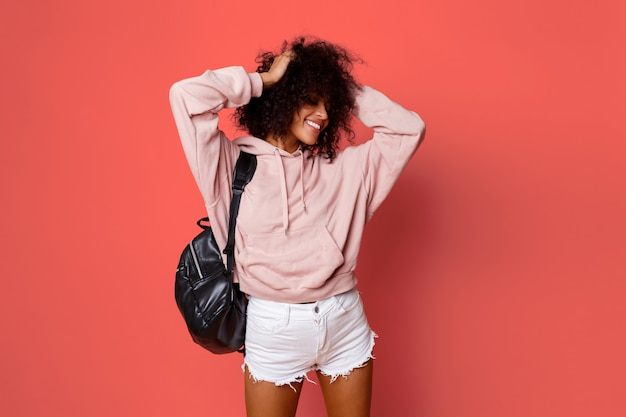 Free Photo   Lovely sexy black woman in stylish hoodie with back pack  posing on pink background and playing with curly hairs.